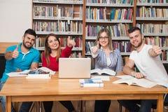 Studenti in una biblioteca che mostra i pollici su Fotografia Stock
