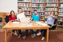 Studenti in una biblioteca che mostra i pollici su Fotografia Stock Libera da Diritti