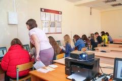 Studenti in una classe del computer con un insegnante immagine stock