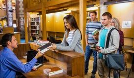 Studenti in una fila al contatore delle biblioteche Fotografie Stock Libere da Diritti