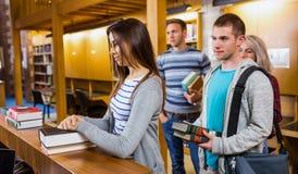 Studenti in una fila al contatore delle biblioteche Immagini Stock