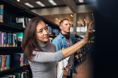 Studenti universitari che prendono libro dallo scaffale in biblioteca Fotografia Stock