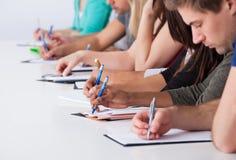 Studenti universitari che scrivono allo scrittorio Fotografia Stock