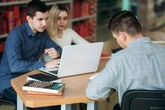 Studenti universitari che si siedono insieme alla tavola con i libri ed il computer portatile I giovani felici che fanno il grupp Fotografie Stock Libere da Diritti