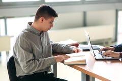Studenti universitari che si siedono insieme alla tavola con i libri ed il computer portatile I giovani felici che fanno il grupp Fotografia Stock
