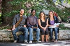 Studenti universitari che si siedono sul parapetto alla città universitaria Fotografia Stock