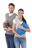 Studenti universitari che tengono i dispositivi di piegatura e gioco del calcio Fotografia Stock