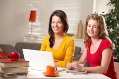 Un ritratto di due ragazze con il computer portatile Immagine Stock