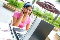 Studentin auf ihrem Mobiltelefon mit einem geöffneten Laptop Lizenzfreie Stockbilder