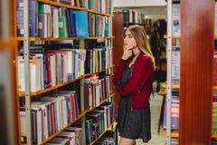 Studentin chosinga Buch in der Collegebibliothek getrennte alte Bücher Lizenzfreie Stockbilder