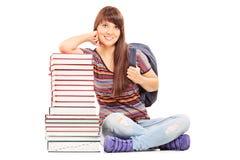 Studentin, die auf einem Stapel von Büchern sich lehnt Stockfotos