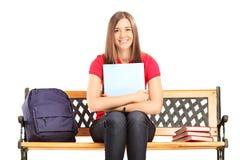 Studentin, die auf einer Holzbank sitzt und ein Notizbuch hält Stockfotografie