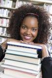 Studentin, die auf Stapel Büchern sich lehnt Lizenzfreie Stockfotos
