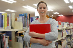 Studentin, die Bücher in einer Bibliothek hält Lizenzfreie Stockfotografie