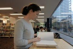 Studentin, die ein Buch in einer Bibliothek liest Lizenzfreie Stockfotos