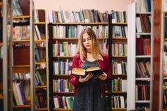 Studentin, die ein Buch zwischen Bücherregalen in der Universitätsbibliothek liest Lizenzfreie Stockfotografie