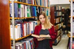 Studentin, die ein Buch zwischen Bücherregalen in der Universitätsbibliothek liest Stockbilder