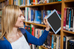 Studentin, die eine Tablette in einem Bücherregal ordnet lizenzfreie stockbilder
