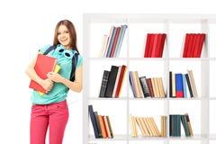 Studentin, die an einem Bücherregal sich lehnt Lizenzfreie Stockfotografie