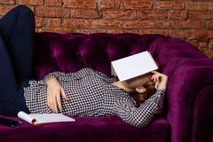Studentin, die erschöpft wird und auf Sofa geschlafen ist lizenzfreies stockbild