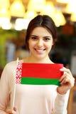 Studentin, die Flagge von Weißrussland hält Stockfotos