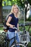 Studentin, die mit ihrem Fahrrad steht Lizenzfreie Stockfotografie
