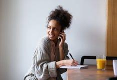 Studentin, die zu Hause arbeitet und am Handy spricht Stockbild
