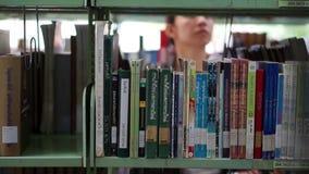 Studentin, die zwischen die Regale, suchend nach Büchern geht stock footage