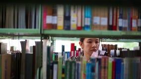 Studentin, die zwischen die Regale, suchend nach Büchern geht stock video