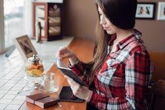 Studentin in einem karierten Hemd, am Nachmittag an einem Café am Fenster, liest einen Block, eine Teekanne mit einem Becher Tee, Lizenzfreies Stockbild