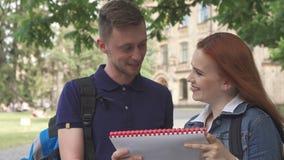 Studentin fragt ihren Mitschüler nach etwas im Notizbuch auf dem Campus lizenzfreie stockfotos