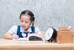 Studentin im einheitlichen Schreiben ihre Hausarbeit stockfotografie