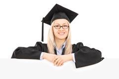 Studentin im Staffelungskleid, das hinter Leerplatte aufwirft Stockbild