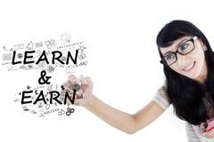 Studentin schreibt Text von Learn und von Earn lizenzfreie stockfotos