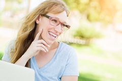 Studentin Wearing Glasses Outdoors, das ihren Laptop verwendet Lizenzfreie Stockfotografie