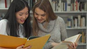 Studentin zeigt ihren Zeigefinger in das Buch auf die Bibliothek lizenzfreie stockfotografie