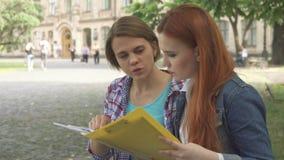 Studentinblick auf irgendeine Zeitschrift auf dem Campus lizenzfreie stockfotos