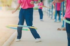 Studentinnen, die Übung mit einem Hulaband für ein gutes healt tun stockfoto