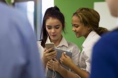 Studentinnen, die Videos auf Smartphone aufpassen stockfotos