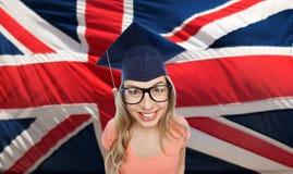 Studentkvinna i akademikermössa över engelskaflagga Royaltyfria Bilder