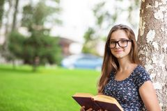 Studentkvinna i exponeringsglas som rymmer en bok som ser dig som ler arkivfoton