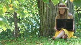 Studentkvinnaarbete med bärbar datordatoren i naturgräsplan parkerar 4K lager videofilmer