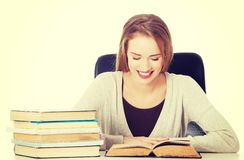 Studentkvinnasammanträde vid skrivbordet med böcker Arkivfoton