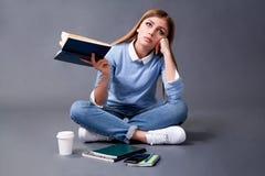 Studentläsebok som sitter på golvet Student Concept studio fotografering för bildbyråer