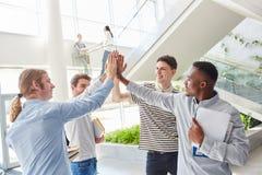 Studentlag som tillsammans sätter händer royaltyfria bilder
