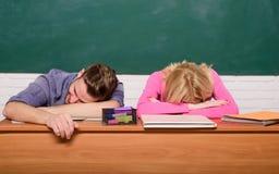 Studentlivfrågor Lutar den trötta eller lata studenten för grabben och för flickan på skrivbordet i klassrum Mening borrat Studer arkivfoto