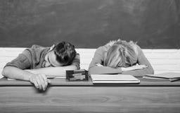 Studentlivfr?gor Lutar den tr?tta eller lata studenten f?r grabben och f?r flickan p? skrivbordet i klassrum Mening borrat Studer arkivfoto
