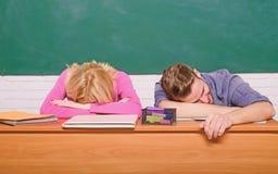 Studentlivfr?gor Lutar den tr?tta eller lata studenten f?r grabben och f?r flickan p? skrivbordet i klassrum Mening borrat Studer royaltyfria foton