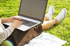 Studentmädchen, das auf dem grünen Rasen tut Hausarbeit auf ihrer Laptop-Computer sitzt Junge Frau, die am blogging Park, wr sitz Stockfotos