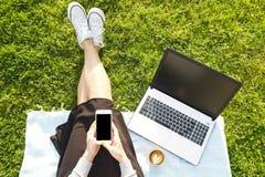 Studentmädchen, das auf dem grünen Rasen tut Hausarbeit auf ihrer Laptop-Computer sitzt Junge Frau, die am blogging Park, wr sitz Lizenzfreies Stockfoto